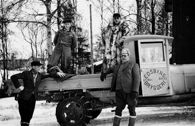"""På fisketur med bryggarbilen 1936. På flaket Åke Söderlund och Axel Larsson """"Bryggar-Lasse"""" väl påpälsad. Nedanför bilen gästerna Zetterberg från Orsa och Fridholm från Osby."""