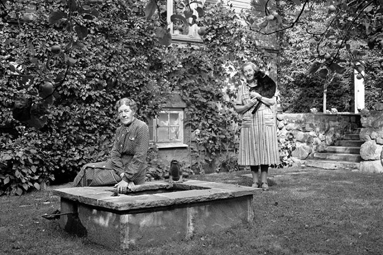 Jenny och Hulda Delander i trädgården på sin gård Morsbacka. Byggd 1918 av fadern Nils Delander. Han var bonde, nämndeman och fjärdingsman och bekant som ledare av sänkningen av sjön Fullen samt insatsen vid Mossbomorden i Alfta. Foto: Stig Elvén 1950.